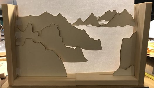 Step 2 - Cut Out the Shape of Mountains and Bird You Need and Set Them on the Wood Frame.