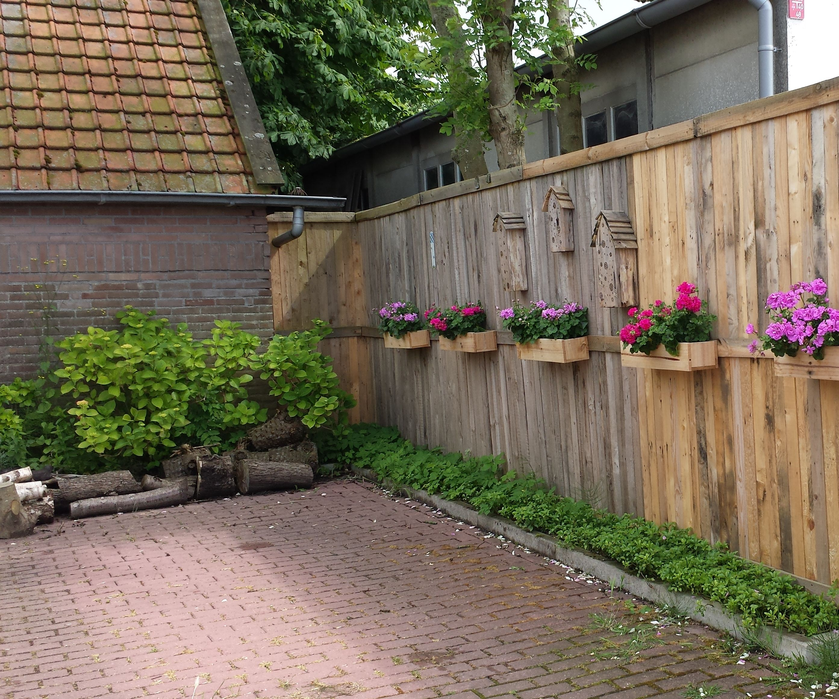 A Pallet Fence with flower boxes and bee hotels