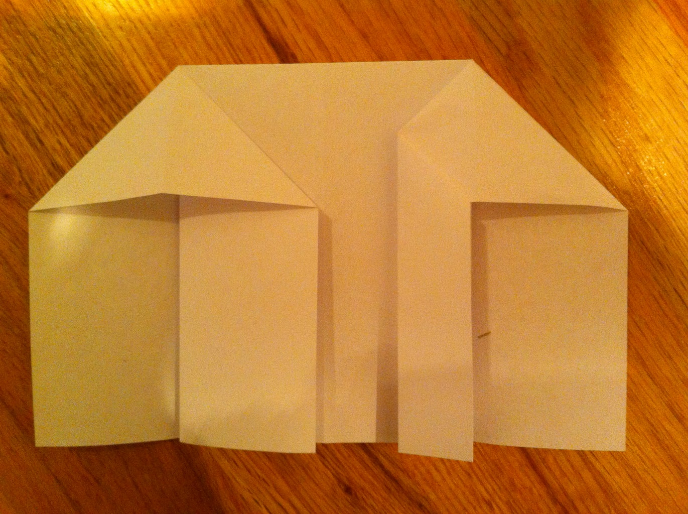 Fold One of the Flaps Halfway to Meet the Center Line of the Triangle.