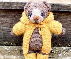 钩针逗人喜爱的被充塞的熊在雨衣和靴子使用针织缝