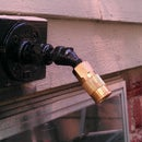 Compressed air bulkhead fitting outside wall of house.