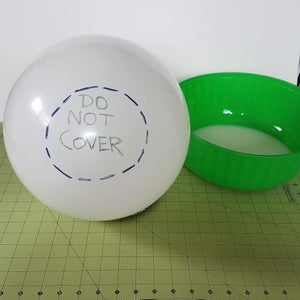 Prepare a Balloon That Is the Size You Want the Mystery Egg to Be.  One Bottom of the Balloon Mark at Place That Will Not Be Cover by Paper Mache.