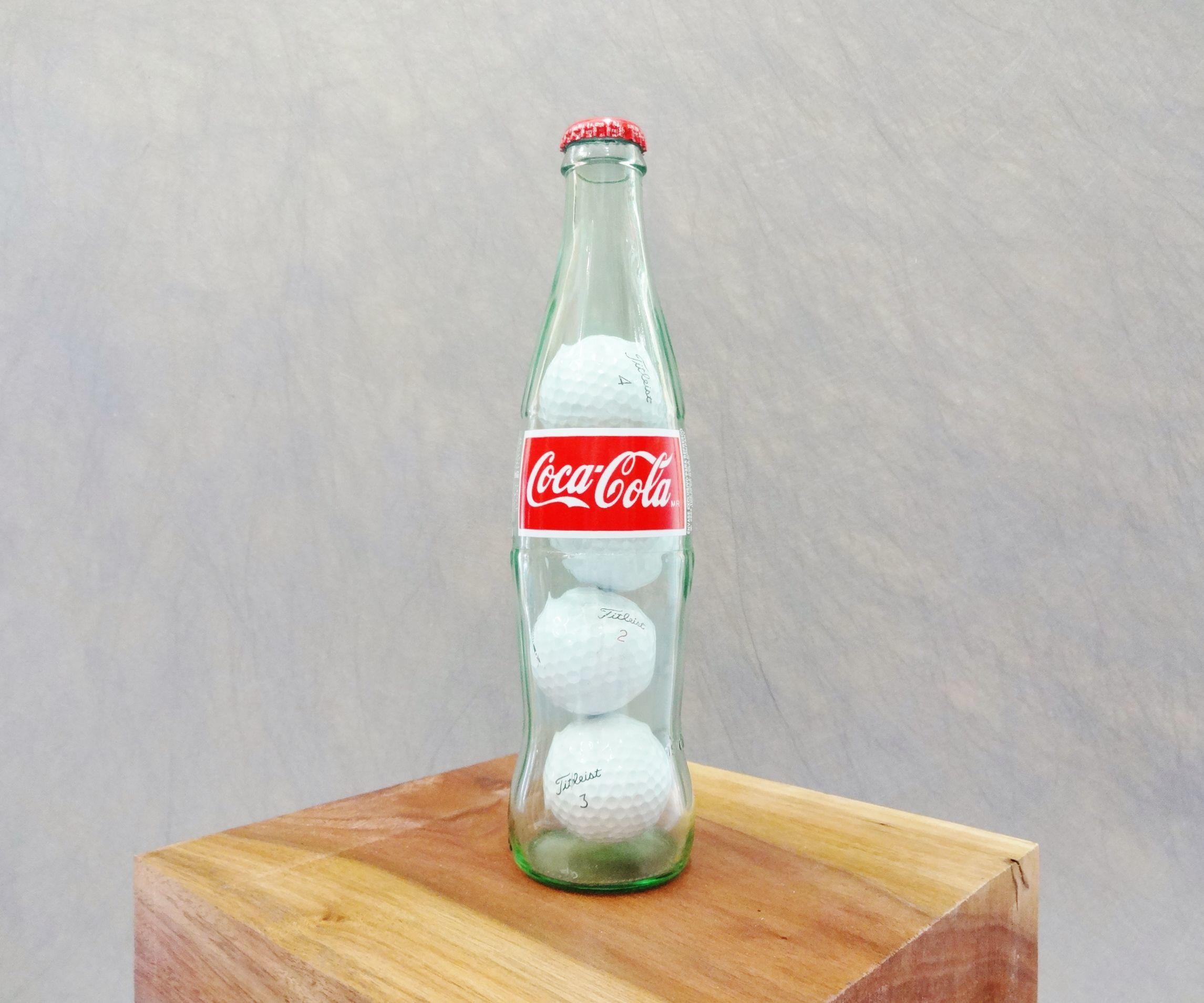 Golf balls in a Coke bottle