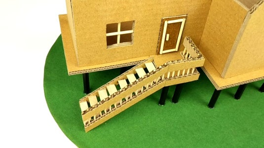 Use the Cardboard and Wooden Sticks to Form the Window, Door and Staircase As Shown. Stick Tissue Paper Behind the Window.
