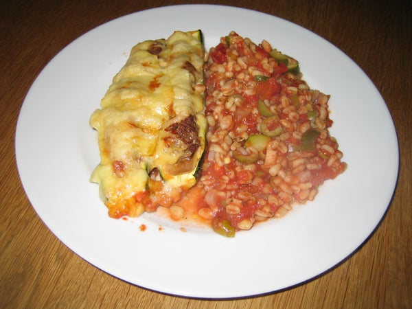 Filled Zucchini Halves on a Mediterran Tomato-wheat Bed
