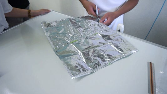 CUT OUT THE GLUED WRAPPERS INTO SEGMENTS USING THE MODEL