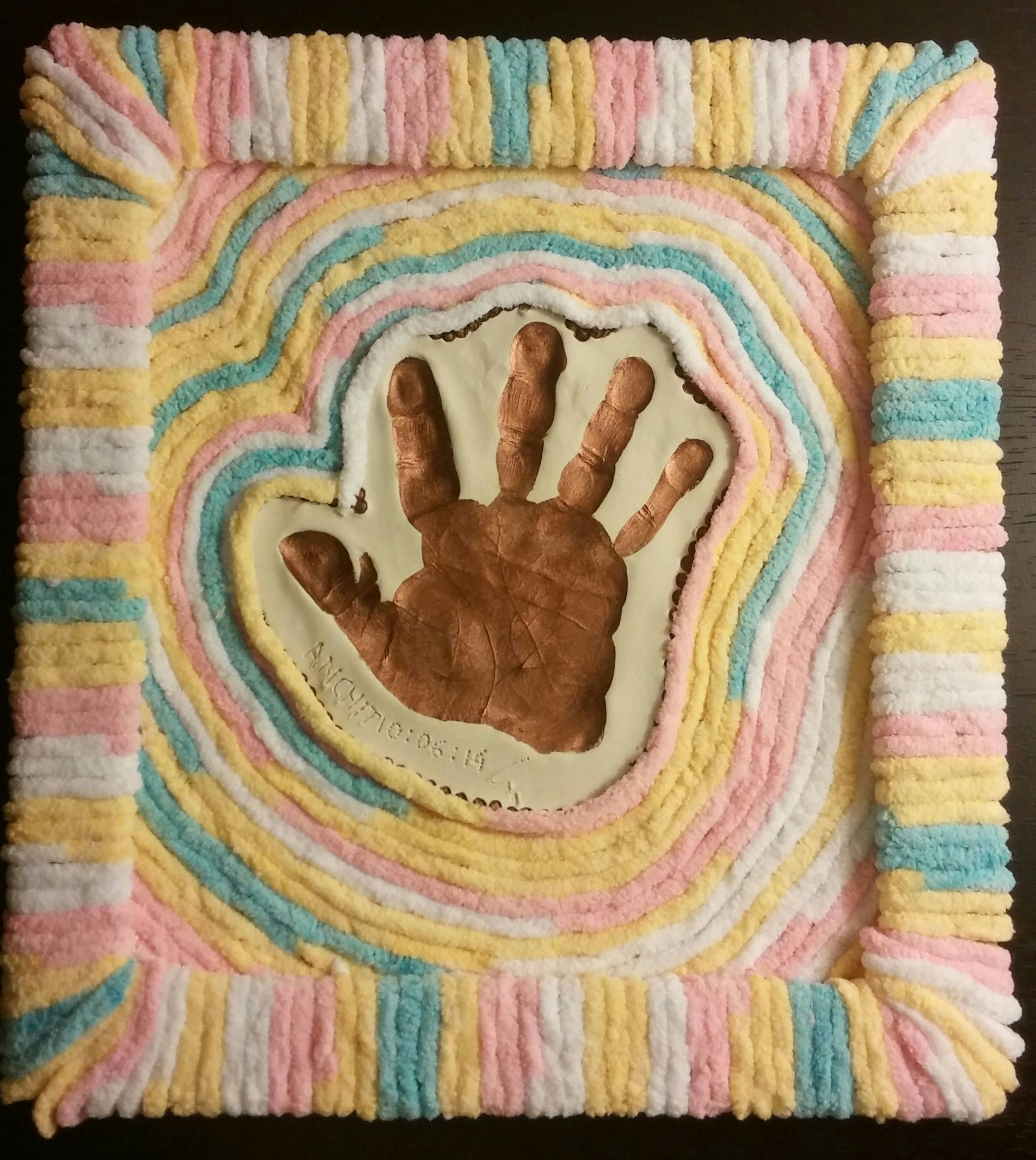 Framed hand-print with yarn and cardboard