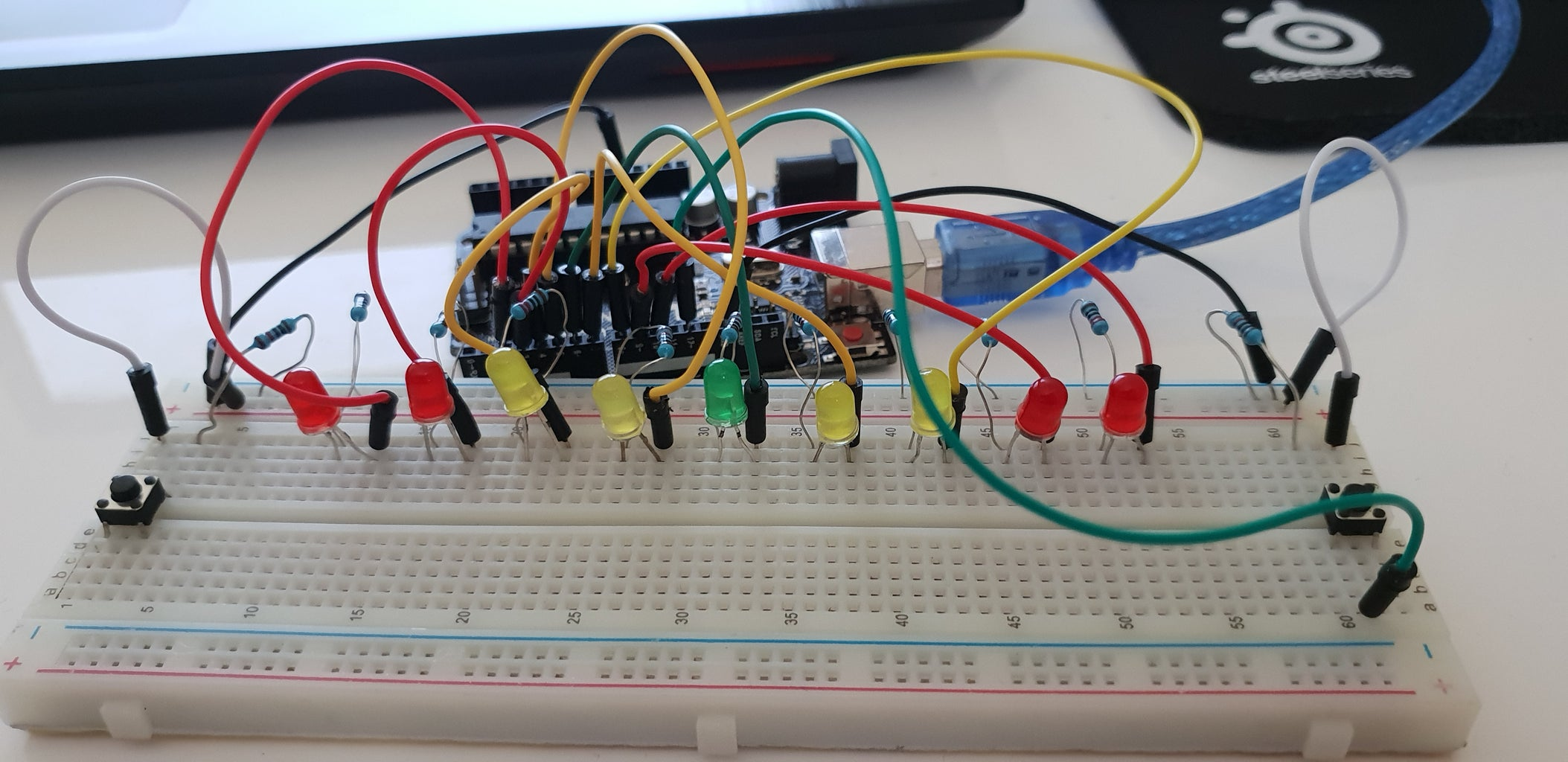 Place a Male to Male 20cm Jumper Cable Under the Bottom Left Leg of the Right Push-Button and Connect It to Number 12 on the Arduino UNO Board As Shown Below