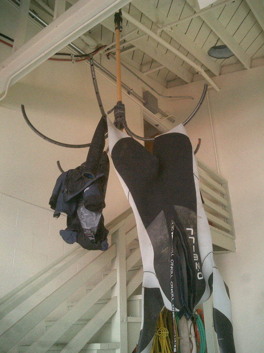 Wetsuit hangers from bicycle rims.