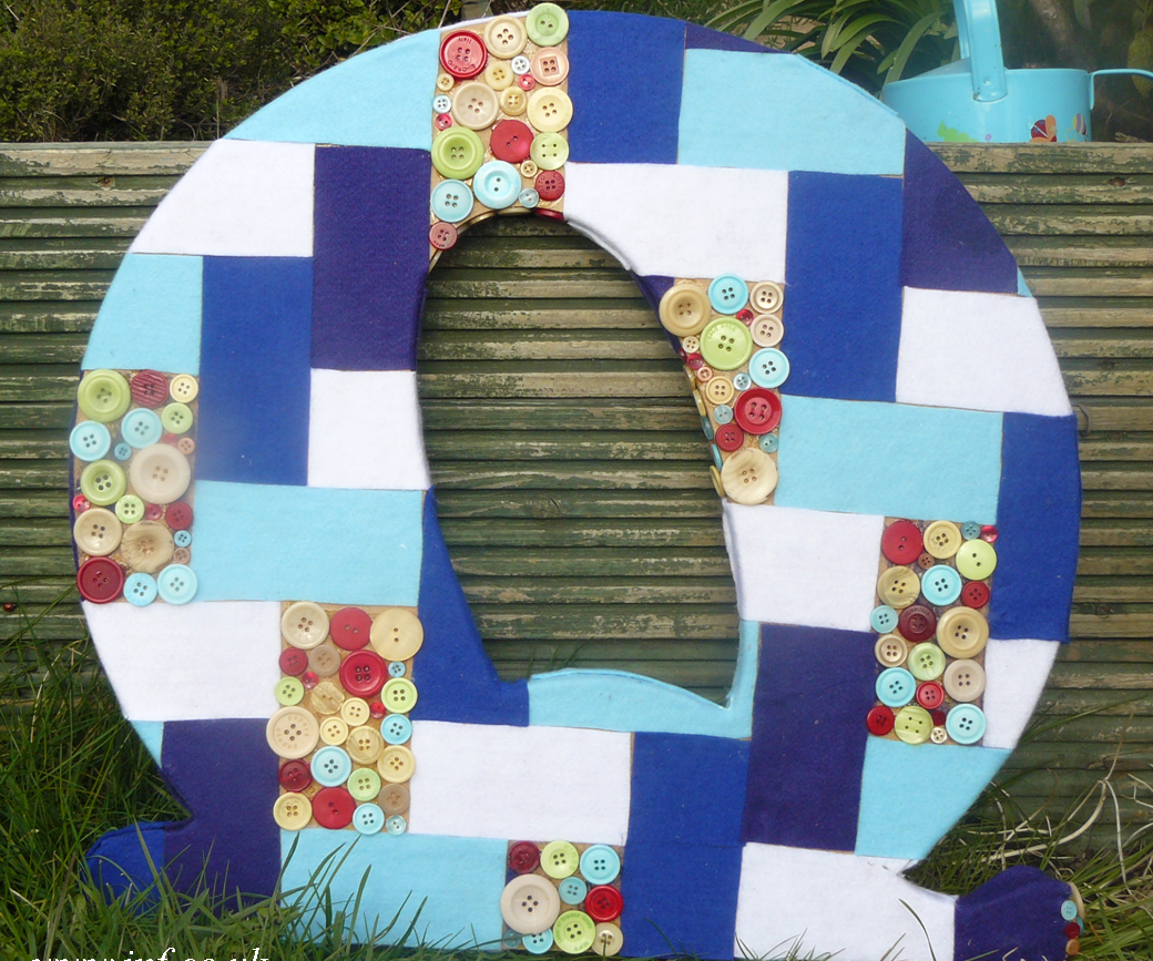 A giant patchwork and button mosaic letter