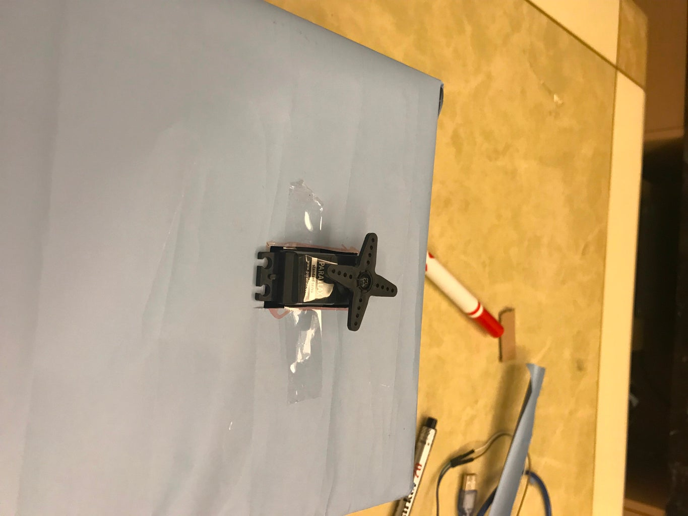 Fit the Servo Into the Rectangular Hole on the Top of the Shoe Box Cable-first in the Direction As Shown in the Picture. Then, Tape the Servo to the Surface of the Box to Make It Sturdy.