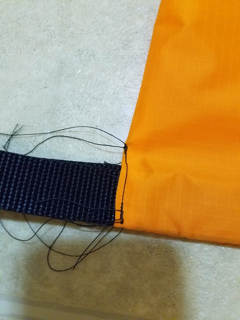 Roll the Top 3 Inches of Bag Fabric Arround the Webbing and Sew It at the Sides