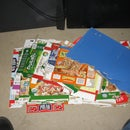 create a GINORMOUS mosaic (visible from space?) using scrap cardboard packaging