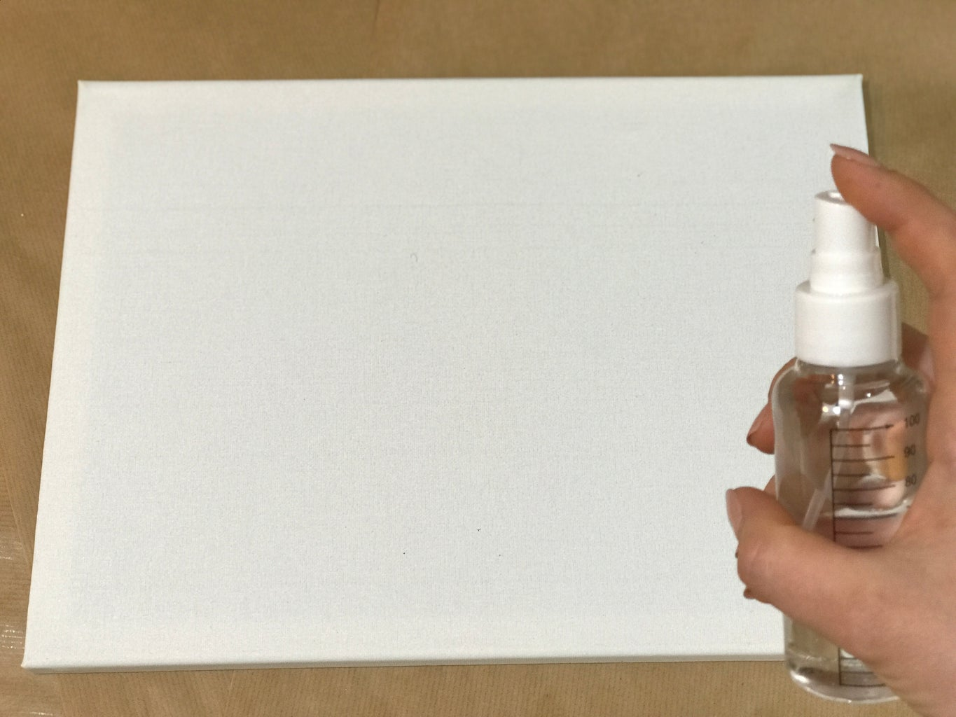 Spray You Canvas With Water and Wipe the Excess With a Sponge.