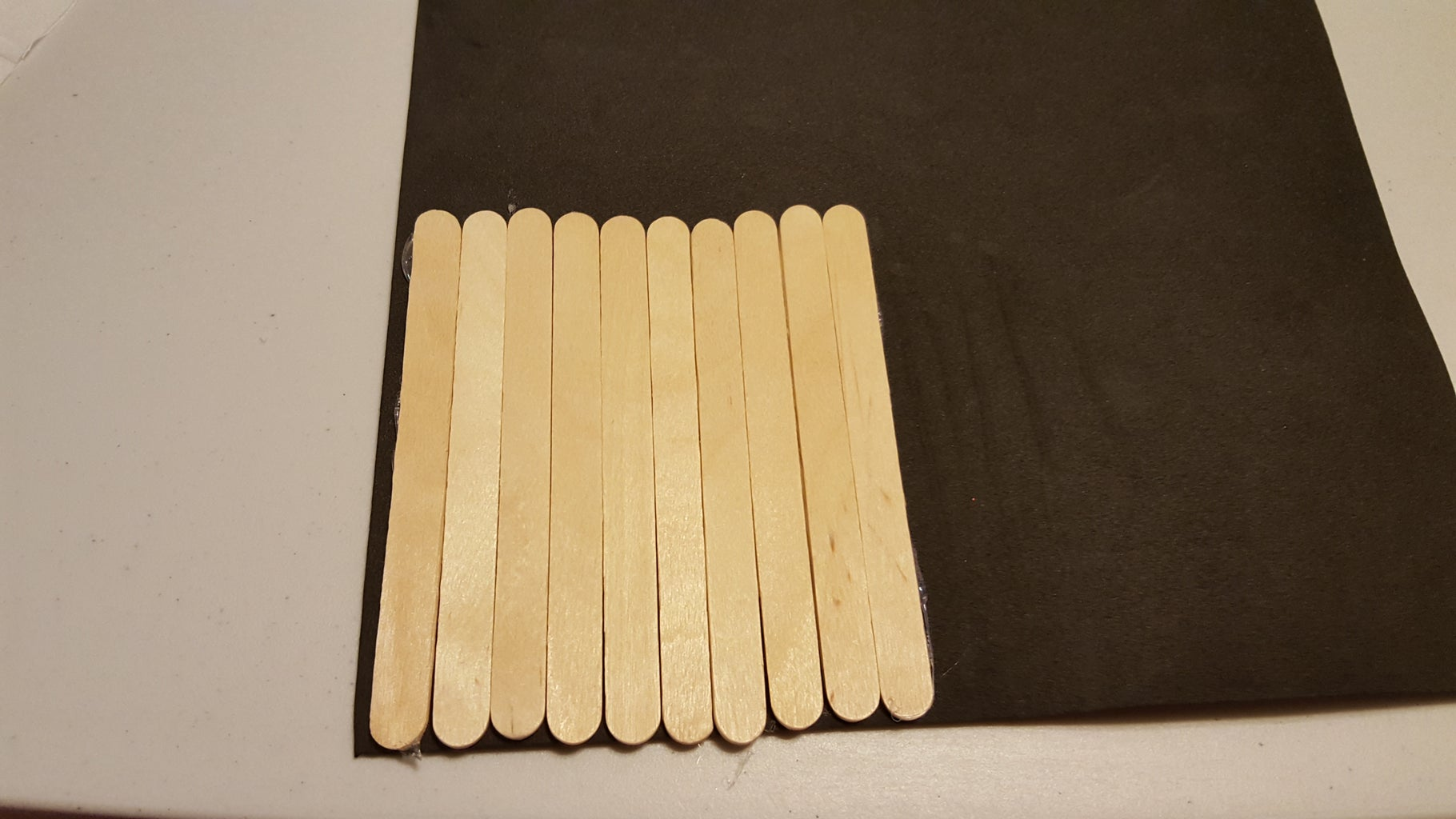 Repeat Steps 4 and 5 Until You've Glued Ten Popsicle Sticks to the Foam Sheet