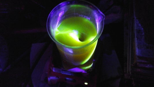 Laser Light Show With Beaker, Yellow Dye, Quinine, Niacin Energy Drink, Mountain Dew, Etc in Water and an Electric Stirrer.