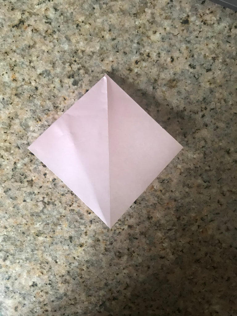 Bring the Top Point Down to the Bottom, While Also Folding the Left and Right Corners Down Into the Center.