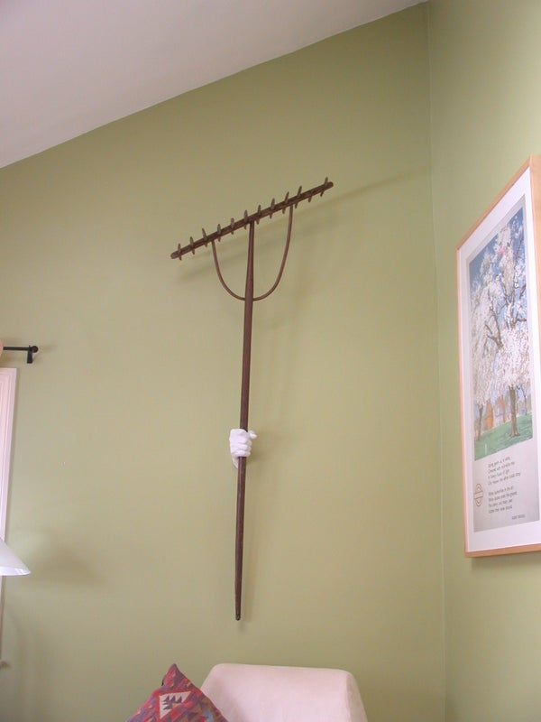 Cast Plaster Hand Mounted to Wall Holds Item for Display.