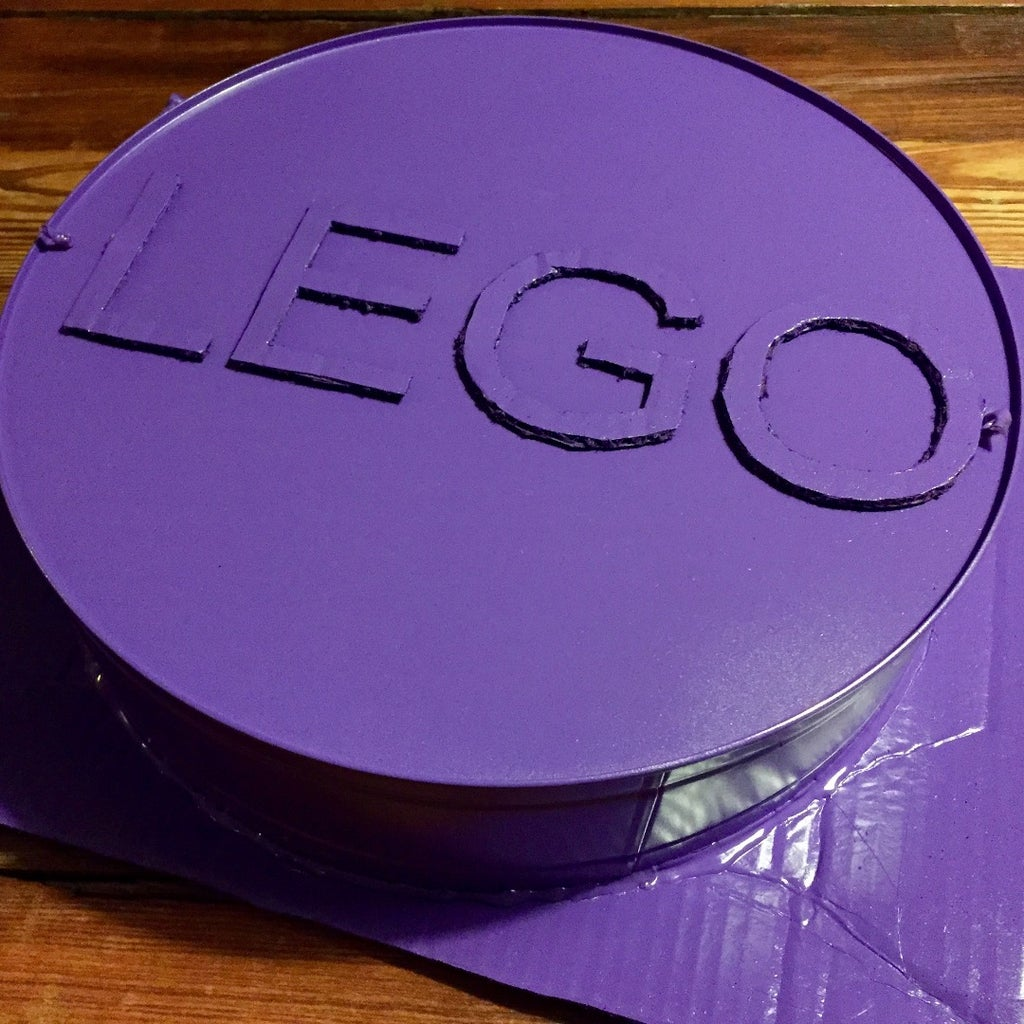 Cut the Letters 'LEGO' Out of Cardboard and Hot-glue to Stud.