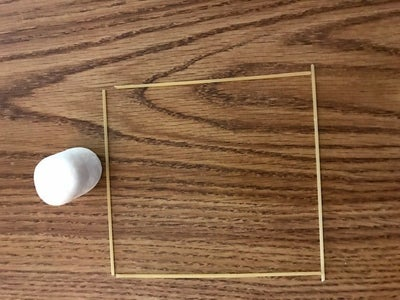 Break 2 Long Pieces of Pasta in Half to Get 4 Smaller Pieces. Lay Them Into the Shape of a Square.