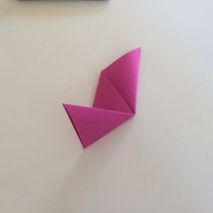 Take One Side of the Triangle and Fold It Up to Make an Ear. Crease.