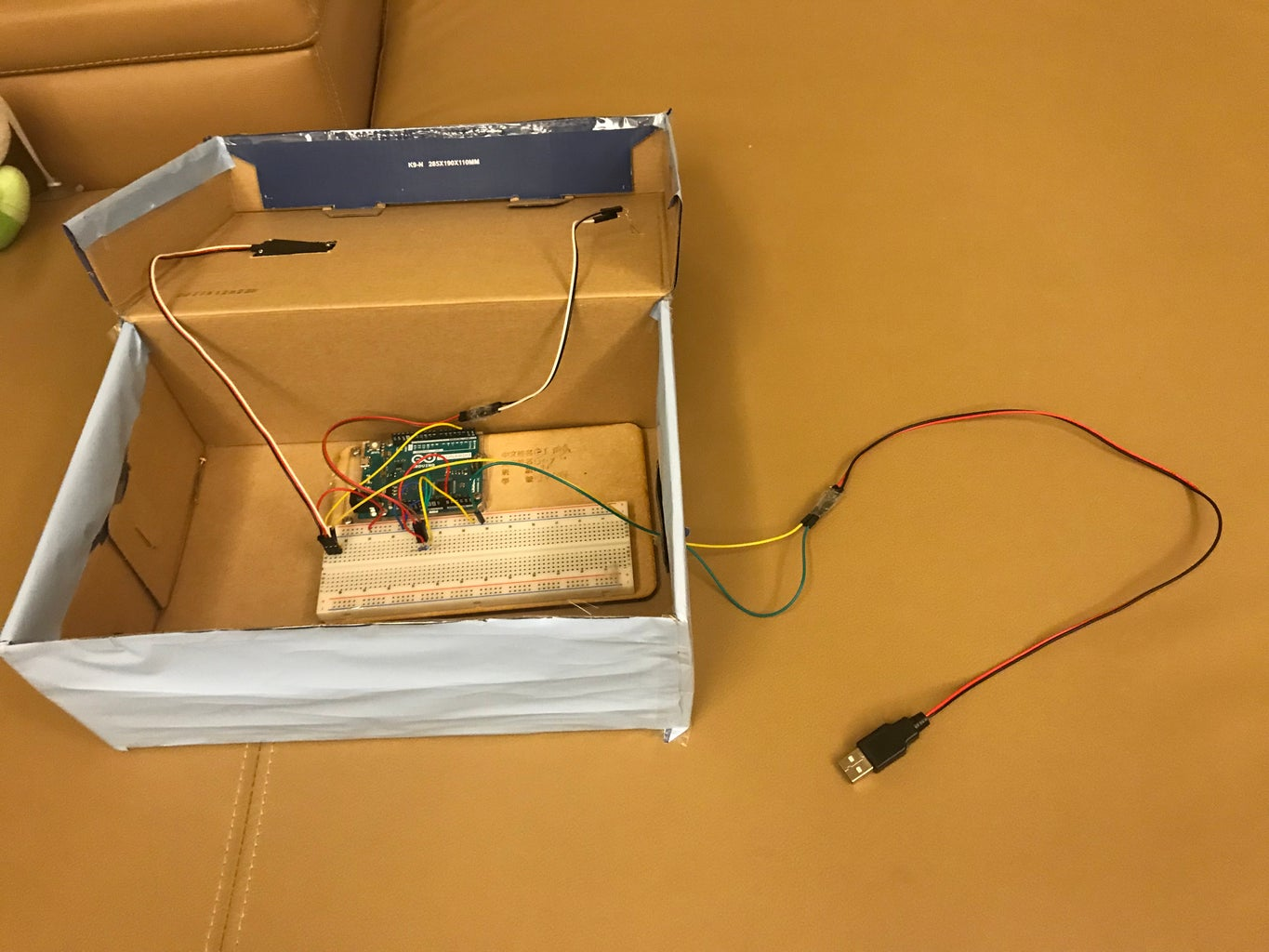 Insert the USB Cable From the Nick on the Side of the Box You've Just Made and Tuck It Into Its Position on the Circuit.